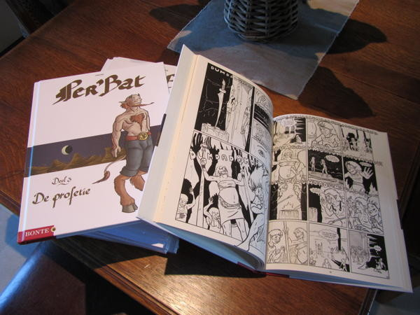 Photograph of a small stack of hardcover Franco-Belgian style comics titled Per'Bat and one opened copy next to it.